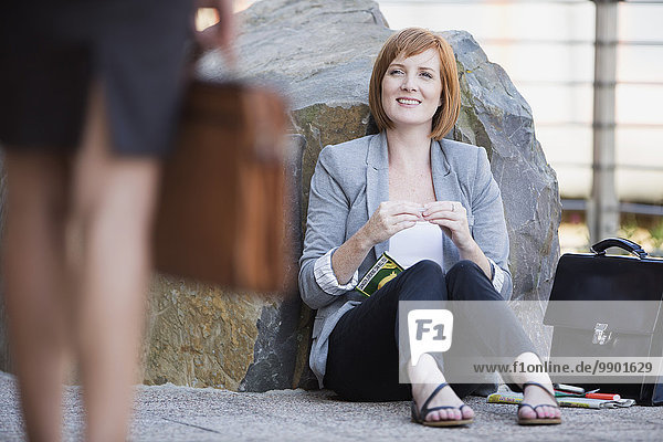 Geschäftsfrau macht eine Pause  sitzt auf dem Boden und rollt die Zigarette.
