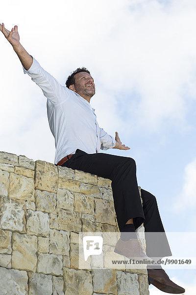 Geschäftsmann auf der Wand sitzend  Arme ausgestreckt