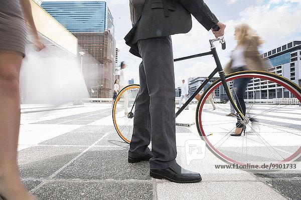 Geschäftsmann  der mit dem Fahrrad zwischen einer Menschenmenge in einer Stadt spazieren geht.