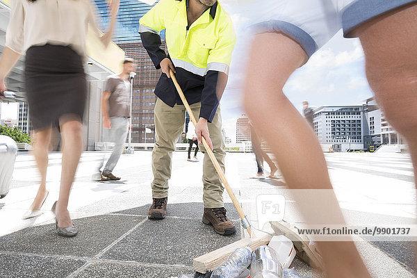 Kommunalreiniger  der Müll zwischen einer Menschenmenge in einer Stadt fegt
