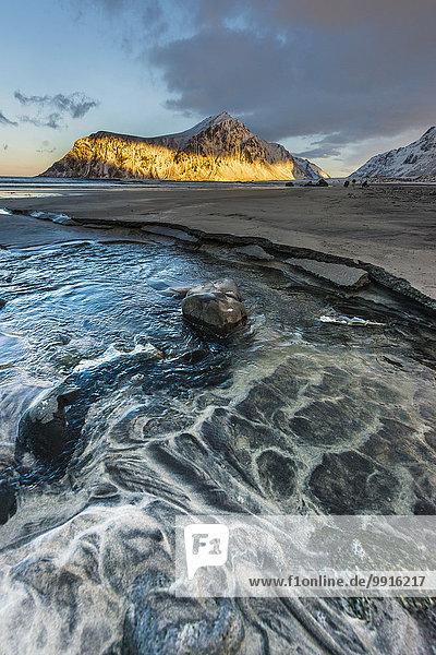 Lichtstrahl fällt auf einen Berg  vorne Strand  Skagsanden  Lofoten  Norwegen  Europa