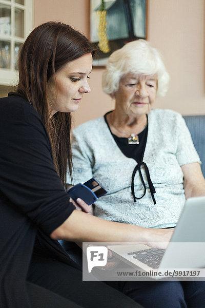 Großmutter und Enkelin mit Laptop zu Hause