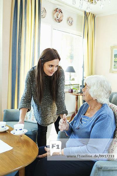 Junge Frau serviert Großmutter Kaffee zu Hause