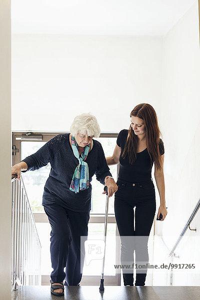 Junge Frau hilft Großmutter beim Treppensteigen