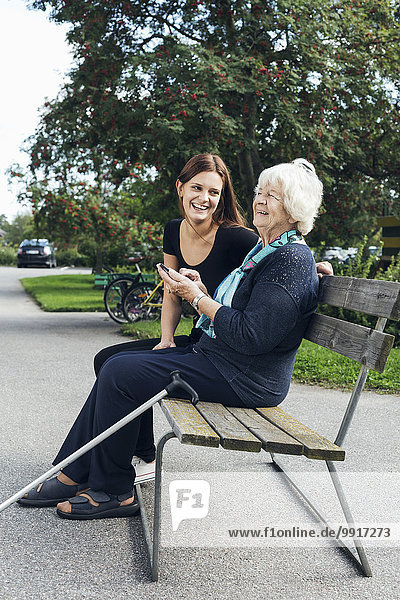 Happy grandmother and granddaughter using mobile phone on park bench