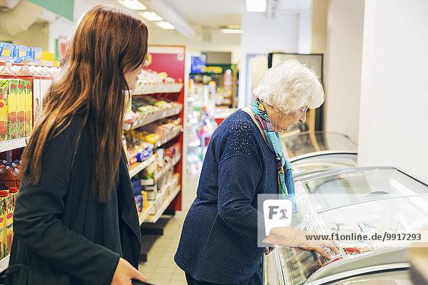 Junge Frau schaut Großmutter beim Einkaufen im Supermarkt zu