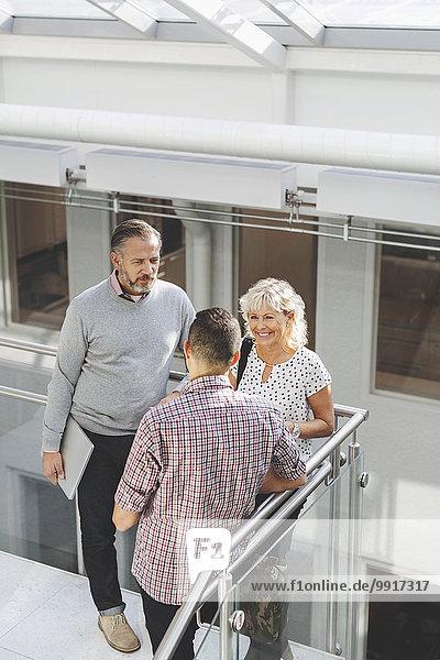 Geschäftsleute diskutieren mit dem Geländer im Büro