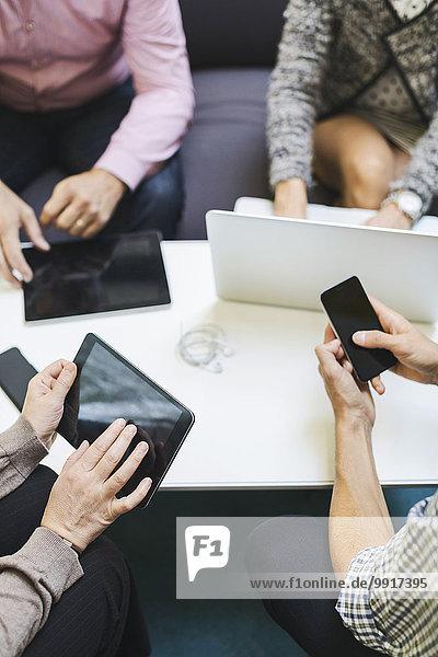 Mittelteil der Geschäftsleute  die Technologien am Tisch im Büro einsetzen