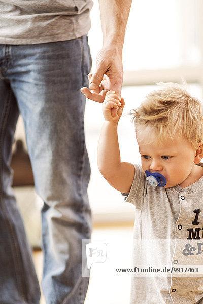 Mittelteil des Vaters mit dem Finger des Babyjungen zu Hause