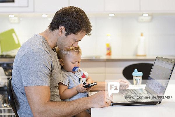Vater mit Laptop  der den kleinen Jungen mit dem Handy am Tisch ansieht.