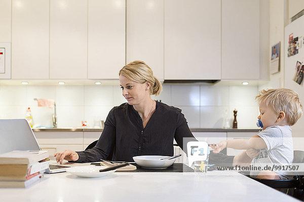 Mutter arbeitet am Laptop  während sie sich um das Baby am Esstisch kümmert.