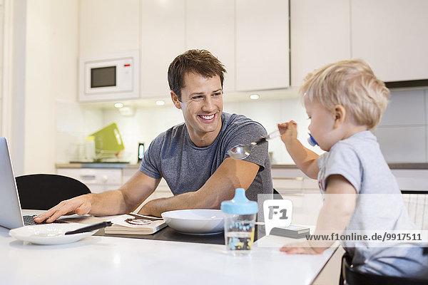 Glücklicher Vater schaut auf den kleinen Jungen  während er den Laptop in der Küche benutzt.