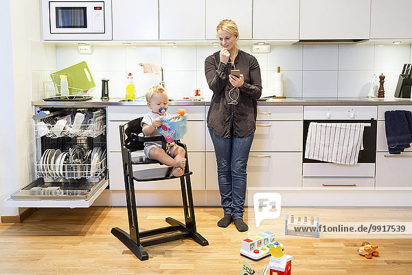 Mutter spricht auf dem Handy in der Küche  während der Junge auf dem Hochstuhl sitzt.