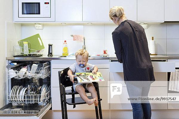 Mutter arbeitet in der Küche  während der Junge auf dem Hochstuhl sitzt.