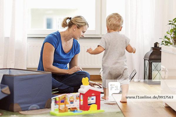 Kleiner Junge  der mit dem Laptop zu Hause auf die Mutter zugeht.