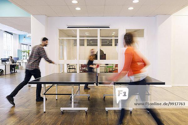 Verschwommene Bewegungen von Geschäftsleuten beim Tischtennisspielen im Kreativbüro