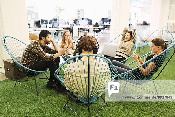 Kreative Geschäftsleute mit Technologien in der Kantine