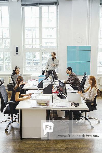Geschäftsleute an Computerschreibtischen im Kreativbüro
