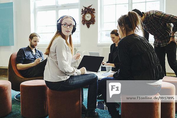 Geschäftsfrau schaut weg  während sie mit Kollegen im Kreativbüro sitzt.