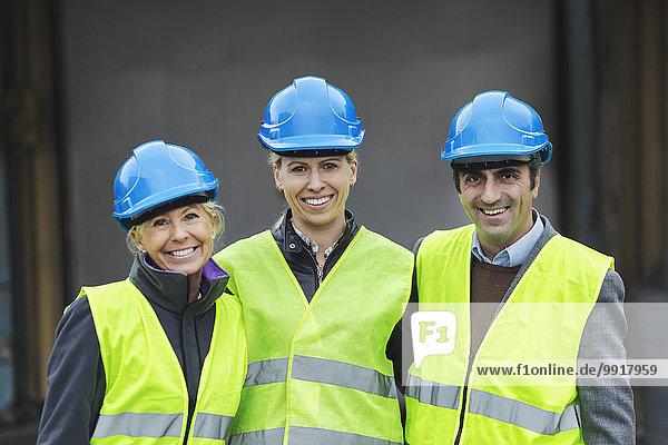 Porträt der selbstbewussten Arbeiter in Schutzkleidung in der Fabrik