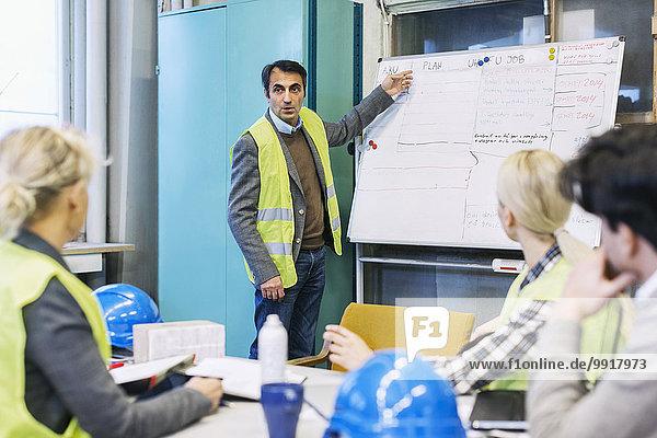 Reife männliche Arbeitskraft erklärt den Kollegen in der Fabrik den Plan auf dem Whiteboard.