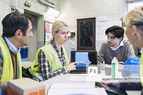 Arbeiterin zeigt Kollegen in der Fabrik etwas auf dem Laptop