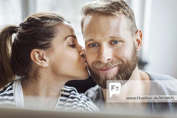 Frau küsst die Wange des Mannes zu Hause