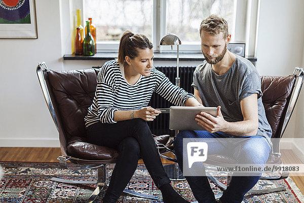Paare online einkaufen  während sie zu Hause auf Stühlen sitzen.