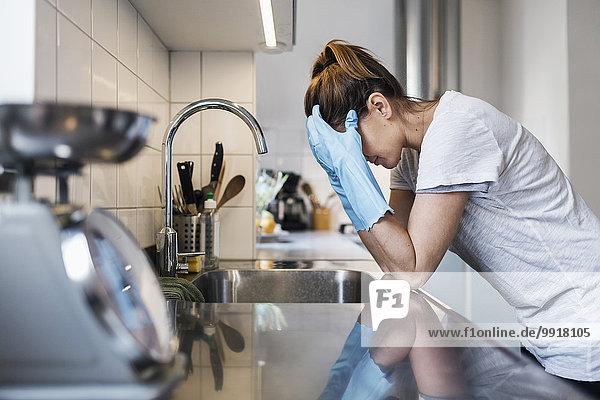 Seitenansicht der angespannten Frau  die sich in der Küche an die Spüle lehnt.
