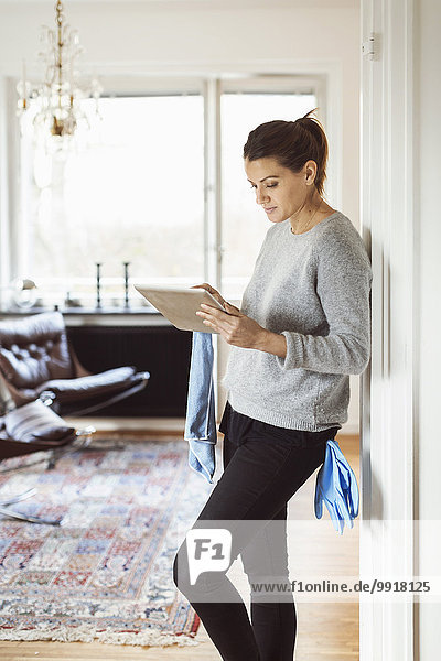 Woman using digital tablet while cleaning home
