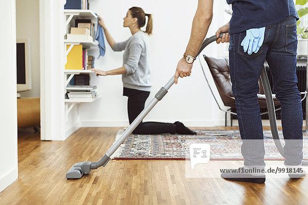 Niedriger Abschnitt des Mannes  der den Boden absaugt  während die Frau die Regale zu Hause im Hintergrund reinigt.