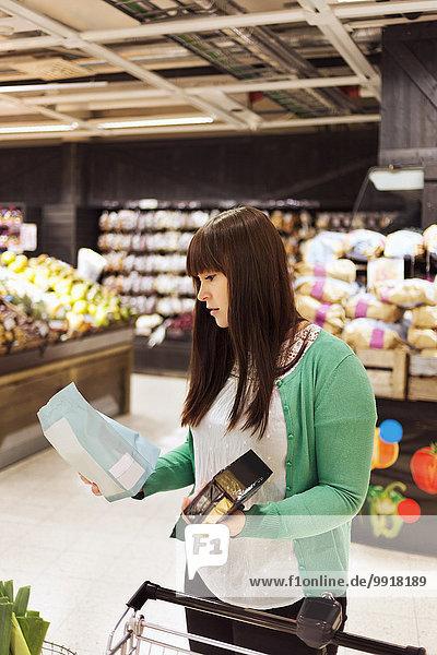 Junge Frau liest Etikett auf Produkt im Supermarkt