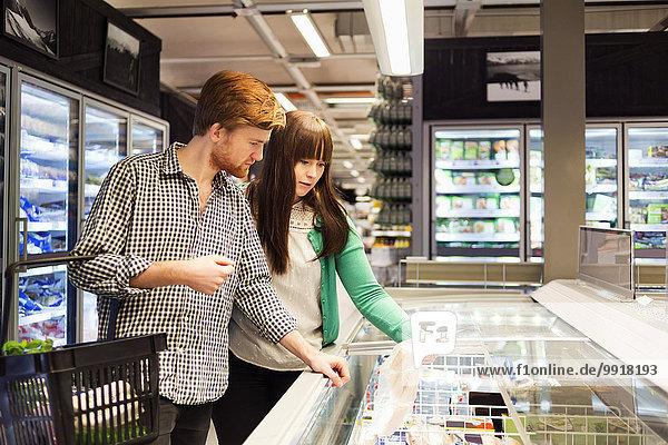 Junges Paar beim Einkaufen in der Tiefkühltruhe im Supermarkt