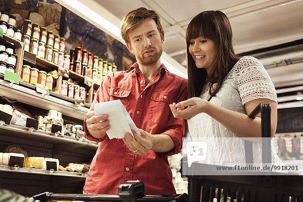 Niedriger Blickwinkel auf die Paar-Leseliste beim Einkaufen im Supermarkt