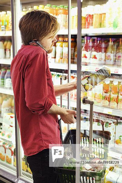 Seitenansicht des Mannes  der beim Einkaufen in der Tiefkühltruhe im Supermarkt das Handy abnimmt.