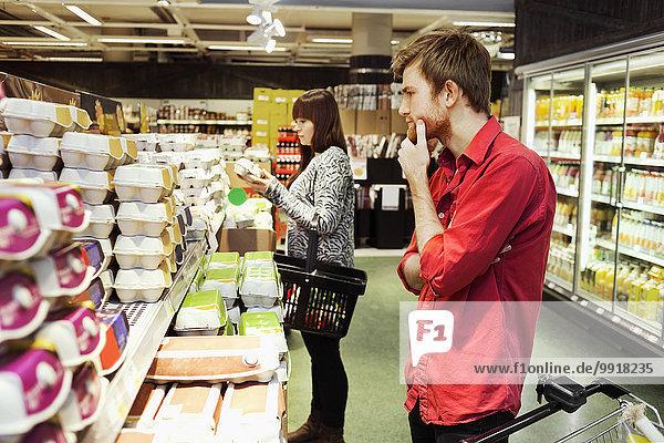 Mann und Frau beim Einkaufen im Supermarkt