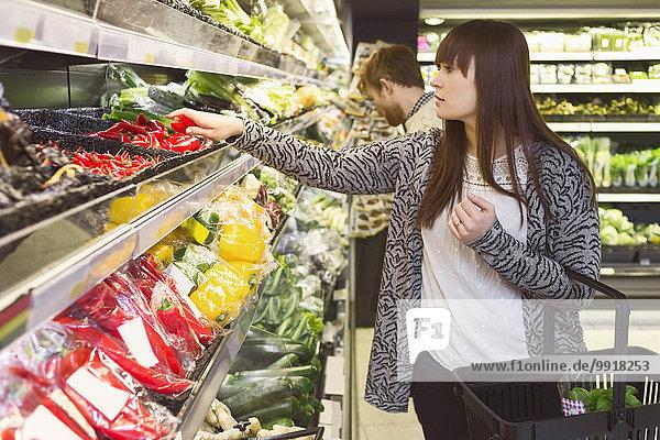 Junges Paar beim Gemüsekauf im Supermarkt