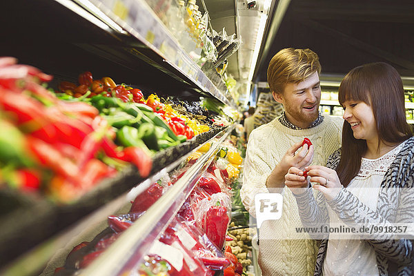 Lächelndes junges Paar diskutiert beim Gemüsekauf im Supermarkt