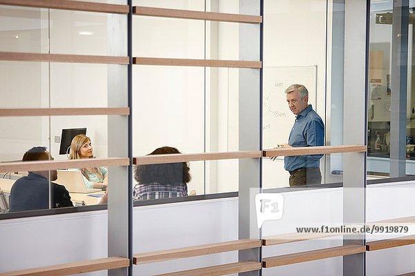 Reife Geschäftsleute bei der Präsentation auf dem Büro-Whiteboard