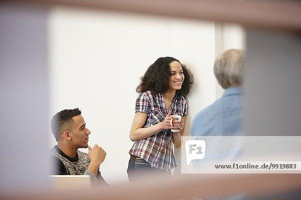 Geschäftsfrau und Männer beim Kaffeetrinken im Büromeeting