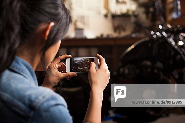 Female mechanic in workshop  taking photograph of motorcycle using smartphone