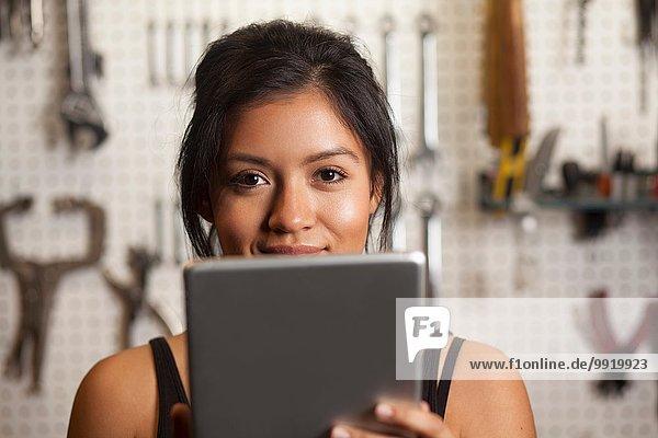 Mechanikerin in der Werkstatt mit digitalem Tablett