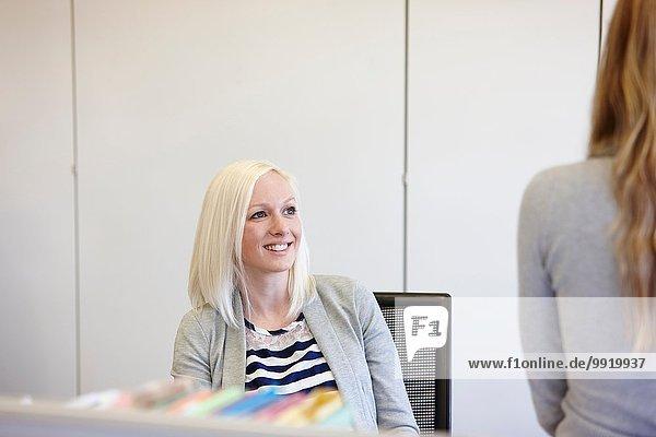 Zwei Geschäftsfrauen im Gespräch am Schreibtisch im Büro