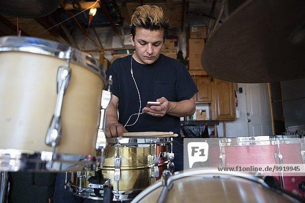 Junger männlicher Schlagzeuger im Keller beim Lesen von Smartphone-Texten