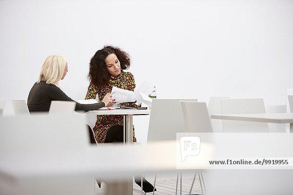 Zwei Geschäftsfrauen prüfen den Papierkram bei der Bürobesprechung