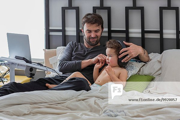 Vater legt Kopfhörer auf Kleinkind Tochter im Bett