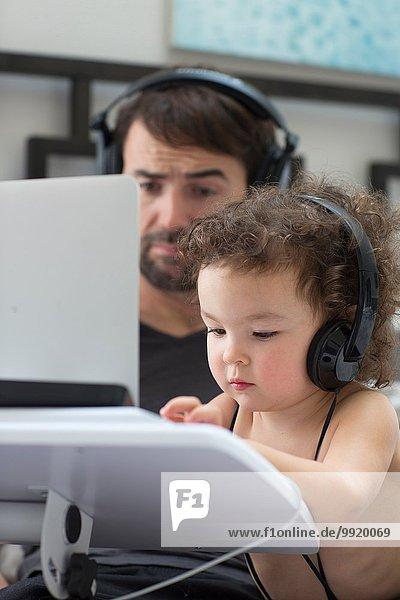 Vater beobachtet Kleinkind Tochter beim Tippen auf dem Laptop  während sie Kopfhörer trägt.