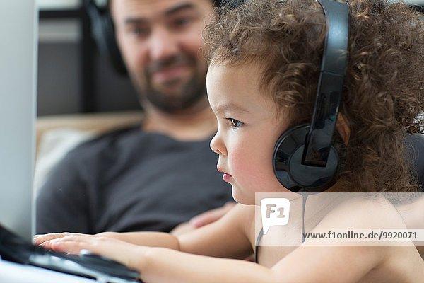 Nahaufnahme des weiblichen Kleinkindes beim Tippen am Laptop,  während Vater zuschaut.
