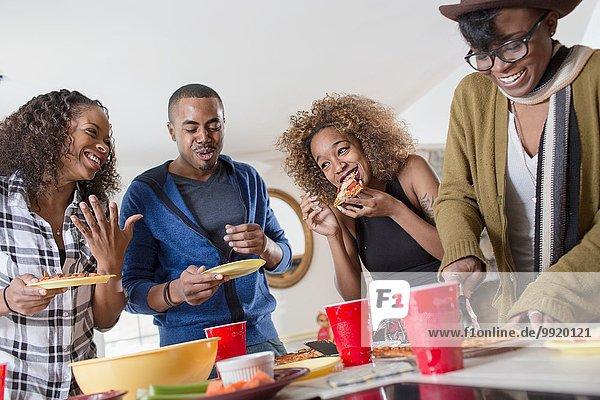 Vier erwachsene Freunde beim Plaudern und Essen in der Küche