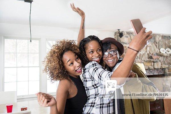 Drei junge Frauen posieren für Smartphone Selfie in der Küche